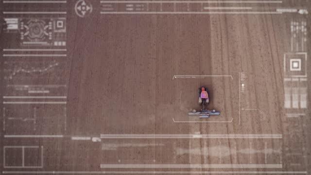 インフィールドで作業しているトラクターをスキャンしながら、未来的なマシンからの航空写真。 - 人里離れた点の映像素材/bロール
