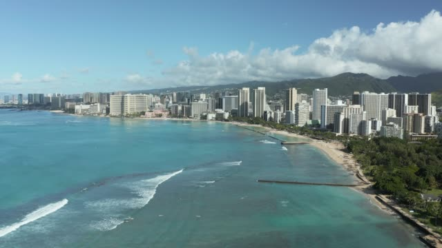 Aerial view from drone with static shot from coast of Waikiki looking towards Honolulu on Oahu
