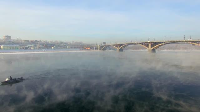 vídeos de stock e filmes b-roll de aerial view from the air. winter. irkutsk city. russia. siberia. view of the bridge across the angara river - irkutsk