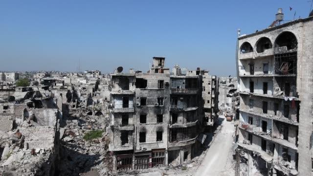 mavi gökyüzü altında, halep 'in harap şehir binaların üst yerden havadan görünüm. suriye 'de bombalamadan sonra harap bir şehrin drone ile görüntüleyin. - coğrafi konum stok videoları ve detay görüntü çekimi