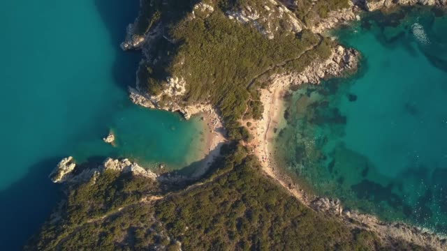 aerial view from the popular tween beach at corfu island in greece. a double-mirrored-gulf beach surrounded by vivid water in an unrealistic way - пелопоннес стоковые видео и кадры b-roll
