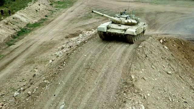 Bидео aerial view - heavy tank overcomes mountain obstacle