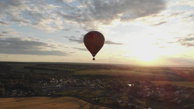 Aerial view: Hot air balloon in sky over field in countryside at beautiful sunset video