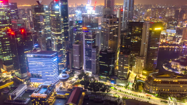 Aerial view hyper lapse of financial central business district building of Singapore city at night with Fullerton Road and Promontory