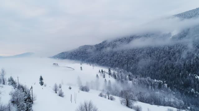 霧のサンセットの冬山で空撮 - ハエ点の映像素材/bロール