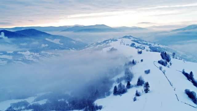 aerial view in foggy sunset winter mountain - aerial mountain stock videos & royalty-free footage