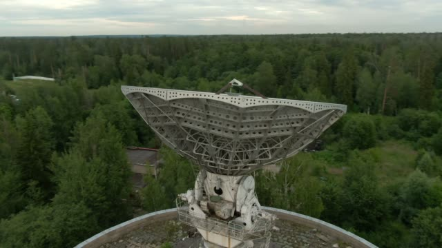 Aerial view is a large space antenna of a radio telescope against the background of a green forest. Space communications equipment
