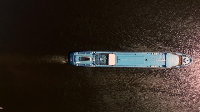 Aerial view journey by passenger ship along the river. Top-down shot from drone