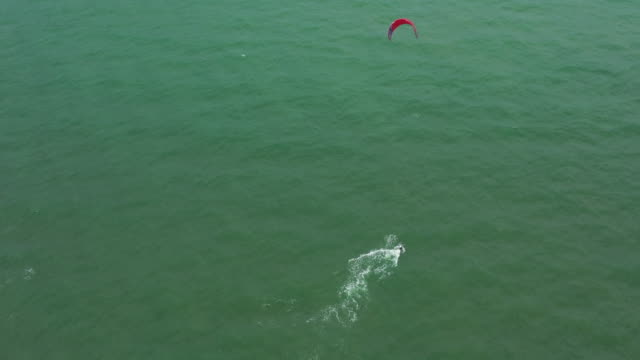 Aerial view kite surfing in sea. Drone view flying ove kite surfer. Kite surfer surfing, Jom Tien Beach, Pattaya, Thailand.