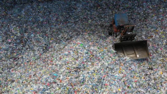 vídeos y material grabado en eventos de stock de vista aérea gran pila de botellas de plástico de desecho en la fábrica para esperar a que se recicle, la conciencia plástica, la contaminación plástica. - bajo posición descriptiva