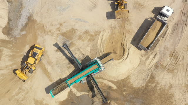 Aerial view loading bulldozer in open air quarry. Sand mining industry. Bulldozer machine. Crawler bulldozer moving at sand mine. Mining machinery working at sand quarry. Drone view of mining equipmen Aerial view loading bulldozer in open air quarry. Sand mining industry. Bulldozer machine. Crawler bulldozer moving at sand mine. Mining machinery working at sand quarry. Drone view of mining equipmen construction vehicle stock videos & royalty-free footage