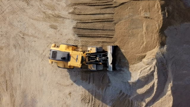 Aerial view loading bulldozer in open air quarry. Bulldozer in action in open air quarry. construction equipment stock videos & royalty-free footage