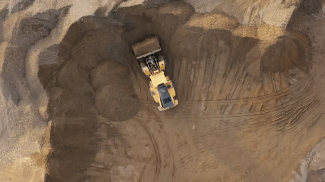 Aerial view loading bulldozer in open air quarry. Bulldozer in action in open air quarry. construction machinery stock videos & royalty-free footage