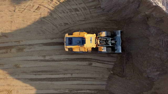 Aerial view loading bulldozer in open air quarry