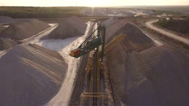 aerial view, machinery working at clay quarry, heavy loaders, large trucks, bulldozers, excavators, sand quarry, mining, the train takes raw materials from the quarry, large clay warehouse - minerał filmów i materiałów b-roll