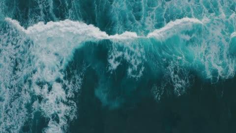 vídeos de stock e filmes b-roll de aerial view ocean waves break into foam along the shore - mar