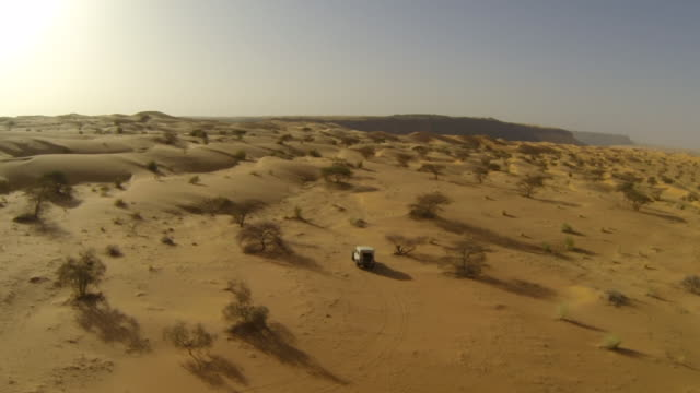 Aerial (drone) view of 4x4 truck driving through remote desert terrain  durability stock videos & royalty-free footage