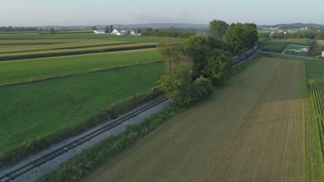 Aerial View of a 1924 Steam Engine with Passenger Train Traveling Along the Amish Countryside as the Sunsets