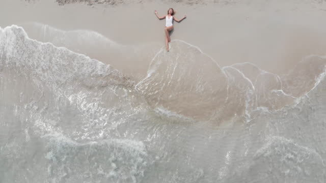 aerial view of a beautiful woman lying on sand in a beach - nazionalità russa video stock e b–roll