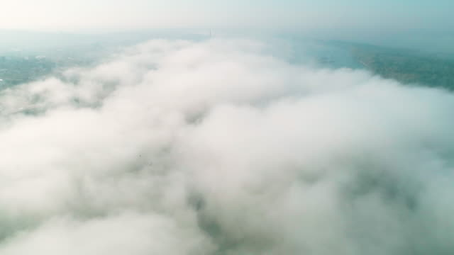 Aerial view of a big cityscape with a thick fog over it, waking up, megapolis from above at sunrise, morning mist.