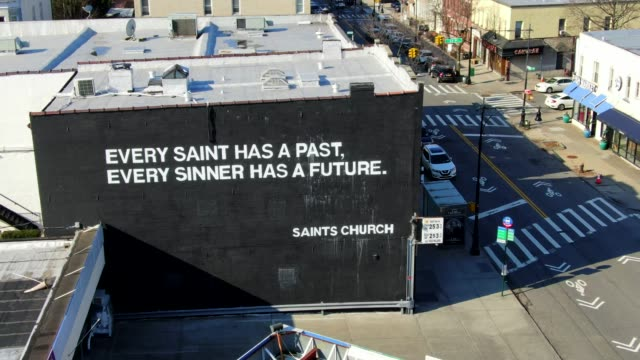 Aerial View of a Black Mural at Saints Church in Queens, NY This is an aerial view of the Saints Church Black Wall Mural.  Saints Church in Glendale, NY.  Saints Church, formerly known as Christ Tabernacle church, is a nondenominationalchurchin NYC with campuses inGlendale, Queens and Bushwick, Brooklyn. mural stock videos & royalty-free footage