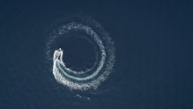 stockvideo's en b-roll-footage met luchtfoto van een boot rijden in cirkels vormen golven rond in griekenland. - boat