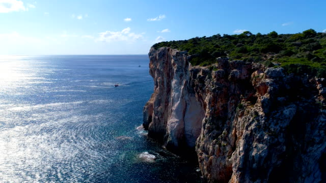 aerial view of a boat in mediterranean sea, with the reflection of the sun in blue water sea. the boat is sailing close to a cliff in minorca, spain. on the cliff, there is only rocks and grass. - mediterranean sea stock videos & royalty-free footage