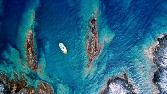 aerial view of a boat on the bay of cap de creus in spain. wonderful view rocks and clear turquoise water of the mediterranean sea. perfect view for summer holidays under the sun. - mar mediterraneo video stock e b–roll