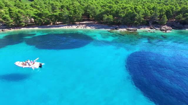 aerial view of a boat passing sandy beach on the island of brac, croatia - хорватия стоковые видео и кадры b-roll