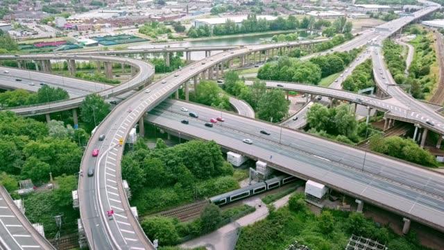 vídeos de stock, filmes e b-roll de vista aérea de uma junção de estrada complexo auto-estrada com tráfego em movimento - entroncamento estrada
