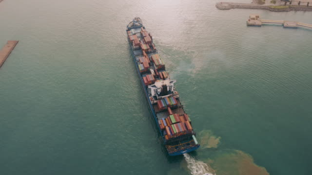Aerial view of a container ship leaving port, freight transportation.