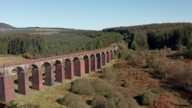 Aerial view of a disused viaduct in remote Scottish countryside 4K drone footage of an old railway viaduct no longer in use galloway scotland stock videos & royalty-free footage