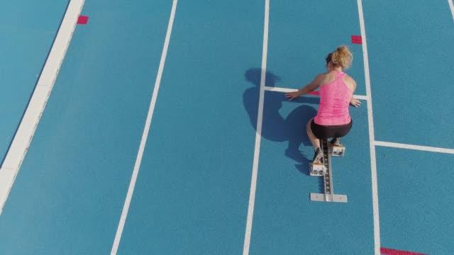 vidéos et rushes de vue aérienne d'une athlète en athlétisme - starting block
