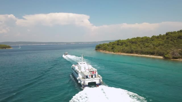Aerial view of a ferry boat with cars loaded, turquoise color sea