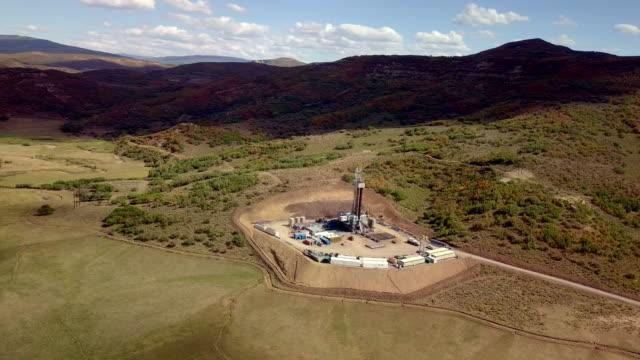 vídeos de stock, filmes e b-roll de vista aérea de um fracking perfuração nas montanhas do colorado de outono - equipamento