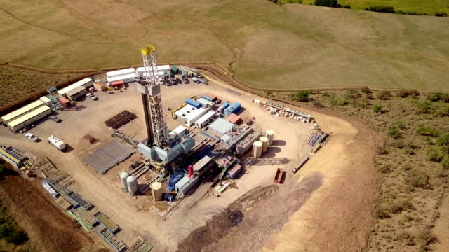 stockvideo's en b-roll-footage met luchtfoto van een fracking drilling rig in de herfst bergen van colorado - olie industrie