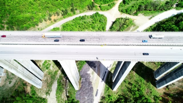 Aerial view of a highway on a viaduct high tech engeneering construction, springtime green colored landscape and clear blue sky