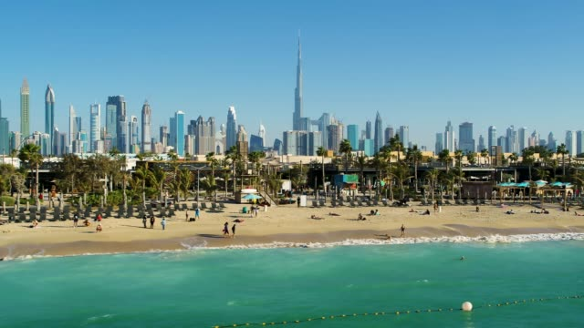 Aerial view of a luxury beach with Dubai skyscrapers at the background, U.A.E. Aerial view of a luxury beach with Dubai skyscrapers at the background, U.A.E. dubai architecture stock videos & royalty-free footage
