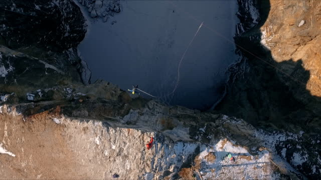 Aerial view of a man jumping off a cliff. Rope jumping. video