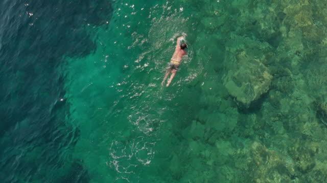 stockvideo's en b-roll-footage met luchtfoto van een man-zwemmen in de egeïsche zee - baai