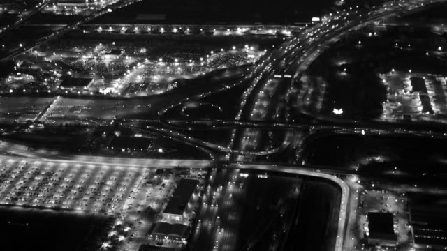aerial view of a modern highway at night. illuminated  multiple lanes. - black and white architecture stock videos & royalty-free footage