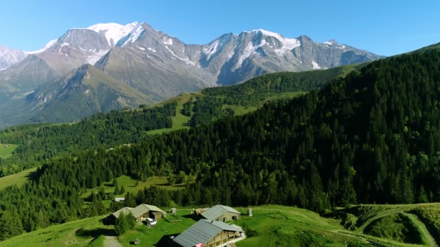 aerial view of a mountain range in the alps, with a chalet down the mountains - france - monte bianco video stock e b–roll