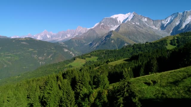 aerial view of a mountain range in the alps, with the peak of mont blanc under the blue sky - france - monte bianco video stock e b–roll