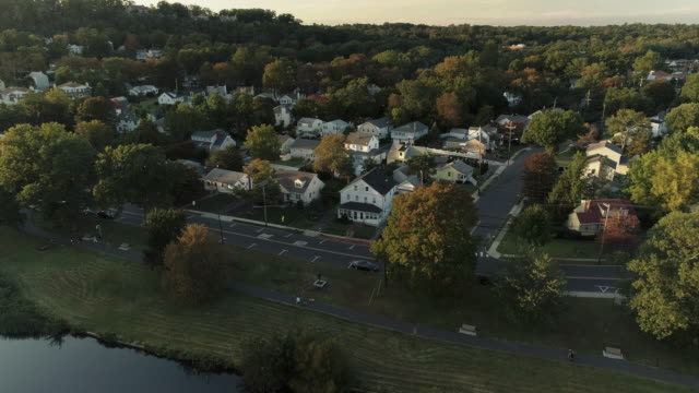 Aerial view of a park and residential area in Springfield, New Jersey, USA, at sunset. Drone video with the ascending and tilting-down camera motion. - vídeo