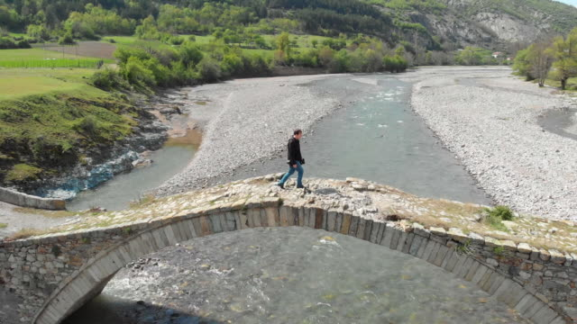 Aerial view of a person crossing a stone bridge