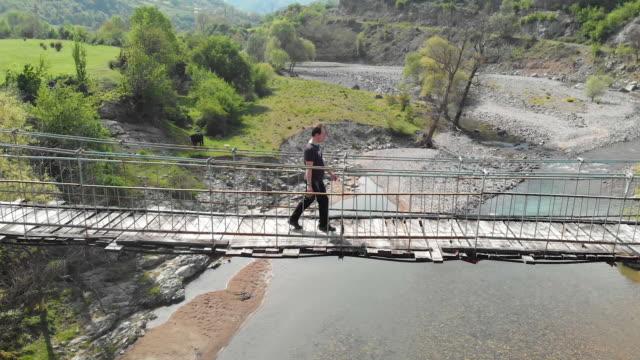 Aerial view of a person crossing a suspension bridge
