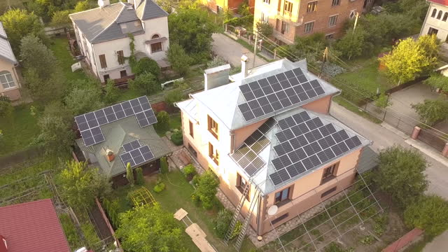 vídeos de stock e filmes b-roll de aerial view of a private house with solar panels on roof. photo voltaic system for renewable energy on building and on the ground. - solar panel