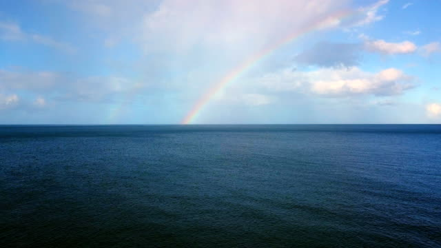 Aerial view of a rainbow over the Caribbean Sea near the Guadeloupe. Panoramic view of a rainbow over the Sea. This is the Caribbean Sea near the Guadeloupe under the blue sky. We can only see the Sea and the rainbow on the horizon. rainbow stock videos & royalty-free footage