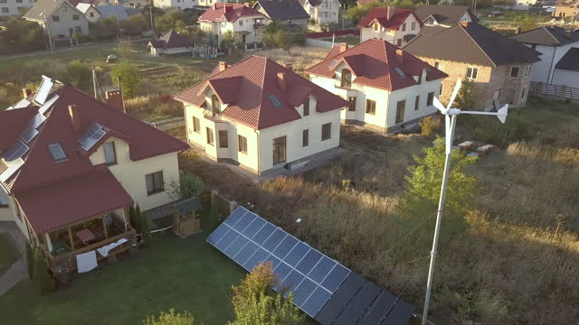 vídeos de stock e filmes b-roll de aerial view of a residential private house with solar panels on roof and wind generator turbine. - solar panel
