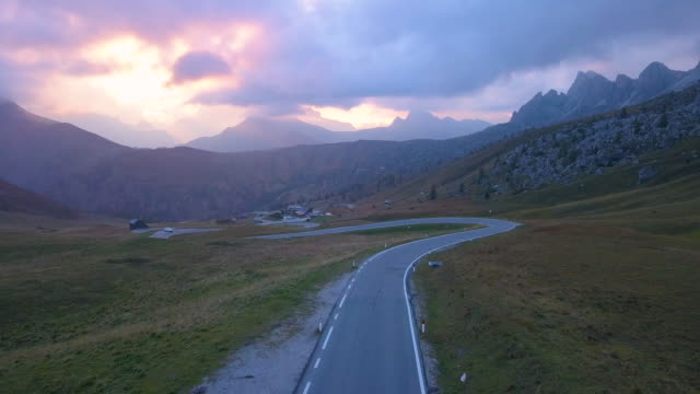 aerial view of a road in dolomites mountains at sunset - strada tortuosa video stock e b–roll